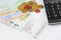 euro bill and coins with chart and calculator - stock photo