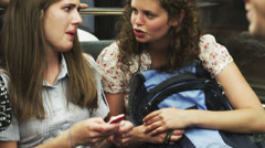 MS Two young women texting on subway train / Paris, France Stock Footage
