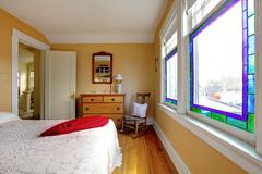 Yellow bedroom with white bed and wood dresser. Stock Photos