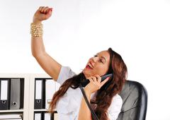 Woman to cheer with uplifted arm in the office Stock Photos