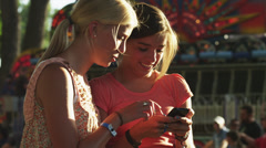 MS Two girls (16-17) using mobile phone in amusement park / American Fork City, - stock footage