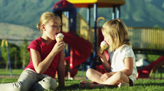 MS SELECTIVE FOCUS Girls(4-11) sharing ice cream, sitting on grass at playground Stock Footage