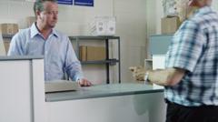 MS TU Elderly man picking up parcel at post office / Orem, Utah, USA Stock Footage