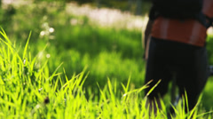 MS PAN Rear view of man with artificial limb riding mountain bike through meadow Stock Footage