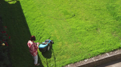 WS HA Woman mowing yard / Rothenburg ob der Tauber, Germany Stock Footage