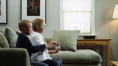 MS Two boys (8-9, 10-11) playing video game, father coming with football ball / Stock Footage