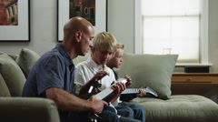 MS DS Father with two sons (8-9, 10-11) learning how to playelectric guitar / Stock Footage