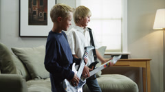 MS Two boys (8-9, 10-11) playing electric guitars in living room / Orem, Utah, Stock Footage