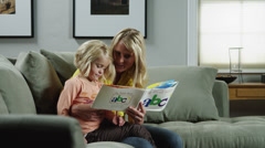 MS DS Mother reading to daughter (4-5) on sofa / Orem, Utah, USA Stock Footage