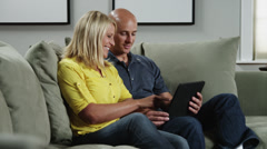 MS DS Woman and man using ipad on sofa / Orem, Utah, USA Stock Footage