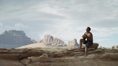 WS DS Man playing guitar on rocks near Lake Powell / Utah, USA Stock Footage