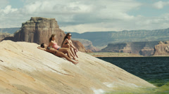 WS Three young women relaxing on rock near Lake Powell / Utah, USA Stock Footage