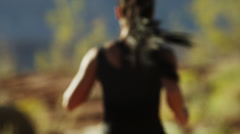 MS FOCUSING Rear view of young woman jogging in desert landscape / Lake Powell, - stock footage