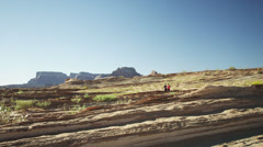 WS DS Young woman and young man jogging in desert landscape / Lake Powell, Utah, Stock Footage