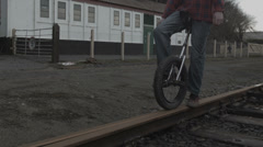 Unicyclist rides rail lines Stock Footage