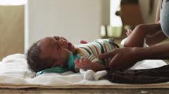 CU TU TD Woman dressing up baby boy (2-5 months) / Cedar Hills, Utah, USA Stock Footage