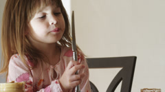 CU Girl (4-5) licking knife in kitchen / Cedar Hills, Utah, USA Stock Footage