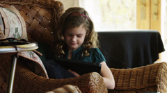 MS ZI Girl (8-9) sitting on wicker armchair and using digital tablet / Cedar Stock Footage