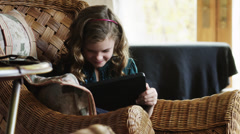 MS ZI Girl (8-9) sitting on wicker armchair and using digital tablet / Cedar - stock footage