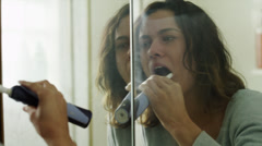 CU PAN Young woman using electric toothbrush in front of bathroom mirror / Stock Footage