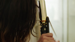CU PAN Young woman using curling iron in front of bathroom mirror / Provo, Utah, Stock Footage
