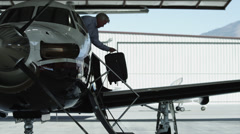 WS PAN Mature man disembarking private airplane and hugging granddaughter Stock Footage