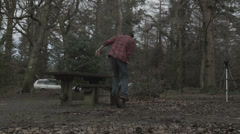 Unicyclist doing tricks on bench in woodland Stock Footage