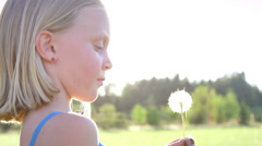 Young blonde girl blows dandelion in the park. - stock footage