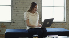 MS DS Young woman using laptop in an office lobby / Salt Lake City,Utah,USA Stock Footage