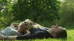 MS Young couple relaxing on lawn in Green Park / London, UK Stock Footage