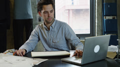 MS Young man working in office holding drawing against laptop / Salt Lake Stock Footage