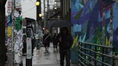 MS Men with umbrella walking on street / Seattle,Washington,USA Stock Footage