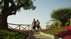 WS Couple walking down path,picking flower from flower bed / Stock Footage