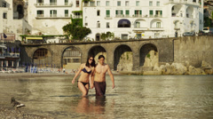 WS Young couple wading in water on Amalfi Beach / Italy Stock Footage