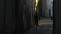 WS Rear view jogging in narrow street of narrow town at dusk / Ravello,Italy - stock footage
