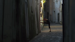 Stock Video Footage of WS Woman stretching in old town alley / Ravello,Campania,Italy