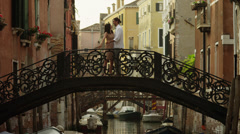 WS Couple standing and kissing on arch bridge across canal / Venice,Veneto,Italy Stock Footage