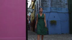 SLO MO MS Woman walking on street,looking at colorful houses / Stock Footage