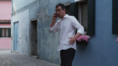 MS Man talking on mobile phone on narrow street in old town / Stock Footage