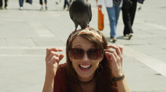 SLO MO CU Portrait of smiling woman with pigeon on head on St. Mark's Square / - stock footage
