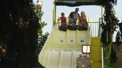 WS Three girls (16-17) going down slide in amusement park / American Fork City, Stock Footage