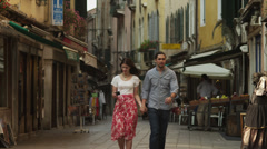 WS Couple taking photographs and walking down old town street / Stock Footage