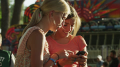 MS Two girls (16-17) using mobile phone in amusement park / American Fork City, Stock Footage