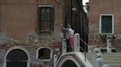 MS Couple walking across small arch bridge / Venice,Veneto,Italy Stock Footage