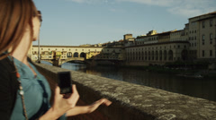 MS Couple walking and taking photographs from water's edge,Ponte Vecchio in Stock Footage