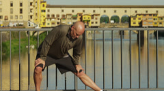 MS Man stretching on bridge with Ponte Vecchio in background / Stock Footage