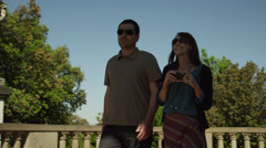 SLO MO MS PAN Couple walking into formal gardens and taking photos / Stock Footage