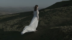 Bride walking up windy hill v4 Stock Footage