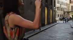 MS PAN Couple taking photos while walking through old town streets / Stock Footage