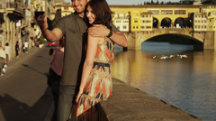 MS TU Couple photographing themselves near Ponte Vecchio / Stock Footage